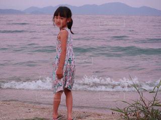水の体の横に立っている女の子の写真・画像素材[1037131]
