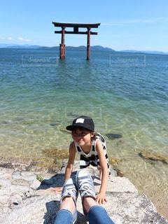 水の体の近くのビーチに座っている人の写真・画像素材[1054782]
