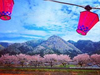 背景の山をフィールドにカラフルな凧の写真・画像素材[1125844]
