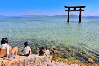 水の体の横に座っている人々 のグループの写真・画像素材[1562724]