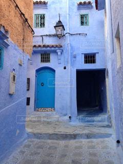 れんが造りの建物の前にある青いベンチの写真・画像素材[1029728]