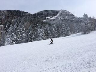 雪に覆われた斜面の下にスノーボードに乗っている男の写真・画像素材[3146749]