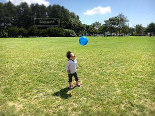 緑豊かな緑のフィールドに立っている少年の写真・画像素材[1029635]