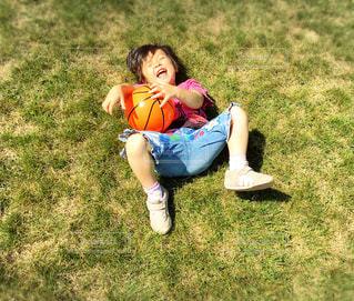 芝生に座っている小さな男の子の写真・画像素材[1029637]