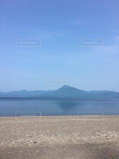 水の体の横にある砂浜のビーチの写真・画像素材[1028744]