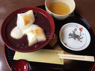 コーヒー カップの横にプレートの上に食べ物のボウルの写真・画像素材[1029497]
