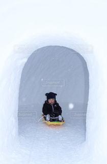 かまくらの中でソリに乗る子どもの写真・画像素材[1029910]