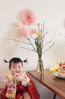 小さな女の子のテーブルに座っての写真・画像素材[1035111]
