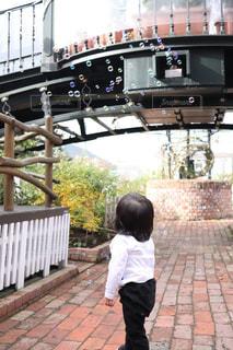 シャボン玉を見つめる娘の写真・画像素材[1616810]