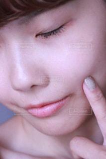 頬を触っている女性の写真・画像素材[1207187]
