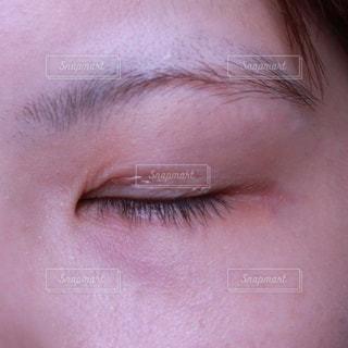 二重化粧品を使っている女性(目を閉じている)の写真・画像素材[1210881]