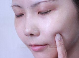 頬を触る女性(スッピン)の写真・画像素材[1215067]