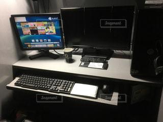デスクトップ コンピューターを机の上に座っての写真・画像素材[1030825]
