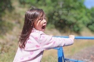 屋外で鉄棒を押している女の子の写真・画像素材[3458975]