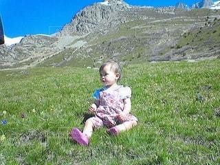 草の中に座っている小さな女の子の写真・画像素材[3476655]