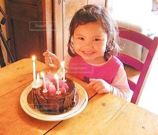 誕生日ケーキの前に座っている小さな女の子の写真・画像素材[3480624]