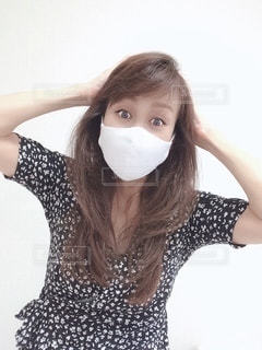 マスクして頭を抑える女性の写真・画像素材[3491257]