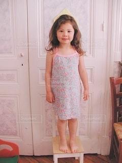 ドアの前に立っているドレスを着た女の子の写真・画像素材[3590166]