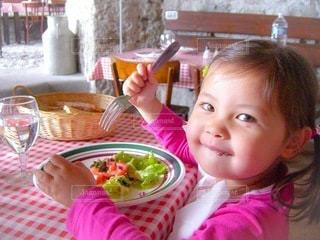 テーブルに座って食べ物を食べる小さな女の子の写真・画像素材[3599298]