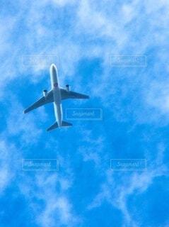 曇った青空を飛んでいる大きな飛行機の写真・画像素材[3670564]
