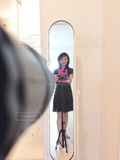 鏡の前に立ってポーズをとる女性の写真・画像素材[3887509]