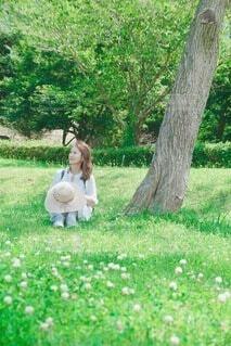 草の中に座っている女性の写真・画像素材[4635084]