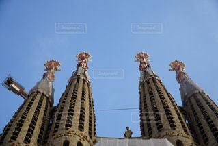 建物の側に時計と大きな背の高い塔の写真・画像素材[1042790]