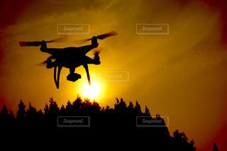 背景の夕日と空を飛んでいるドローンの写真・画像素材[1042905]