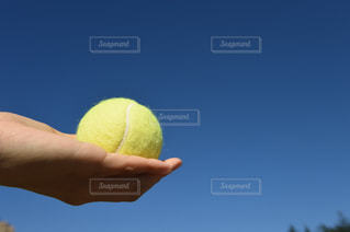 黄色のボールを持っている手の写真・画像素材[1044867]