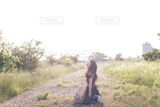 草の覆われたフィールド上を歩く男の写真・画像素材[1223338]