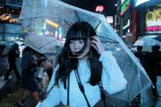 傘を持って通りを歩いて女性の写真・画像素材[1223447]