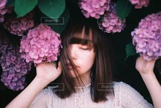 ピンクの花を見た女性の写真・画像素材[2301430]