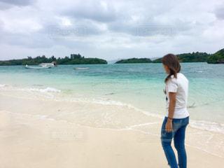 水の体の近くのビーチに立っている女性の写真・画像素材[1039394]