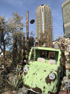 高層ビルの前のボロボロの車の写真・画像素材[1035380]