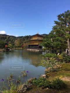 背景に金閣寺と木々 に囲まれた水の体の写真・画像素材[1034909]