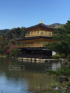 背景の金閣寺の水の体の横に小さな時計塔の写真・画像素材[1034911]