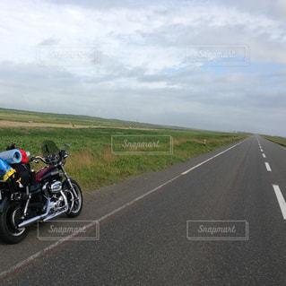 道の端にバイクに乗る人の写真・画像素材[1034060]