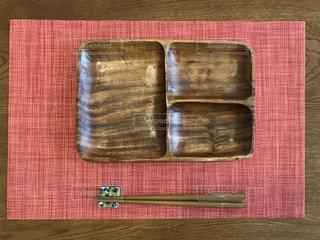赤いランチマットと木製のプレートの写真・画像素材[1081364]