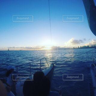 水の体の横に立っている人の写真・画像素材[1034227]