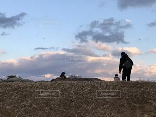 空の雲と草で覆われた丘の上に立っている男 - No.1035218
