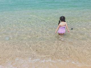 ビーチの砂の上に立っている少女の写真・画像素材[1272009]