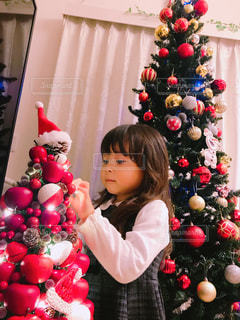 クリスマス ツリーの横に立っている女の子の写真・画像素材[1596063]