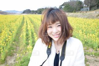 菜の花畑の前での写真・画像素材[1070187]