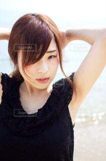 砂浜で髪の毛を束ねる女性の写真・画像素材[1151904]