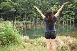 水の体の横に立っている女性の写真・画像素材[1217353]