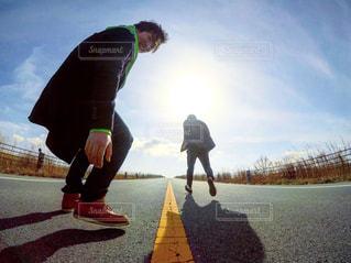 道路の側をスケート ボードに乗って男の写真・画像素材[1036842]