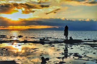 ビーチでの背景の夕日に人々 のグループ - No.1037117