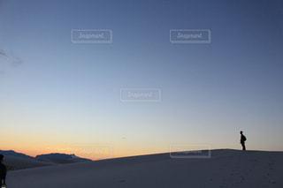 バック グラウンドで夕日を持つ人の写真・画像素材[1037818]