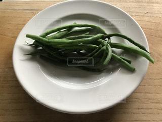 テーブルの上に座って緑と白のプレートの写真・画像素材[1249286]