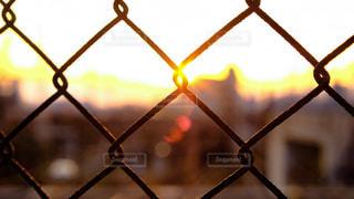 ワイヤー フェンスからぶら下がっている時計の写真・画像素材[1038939]